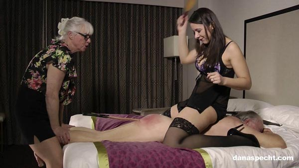 Dana Specht holds her husband's legs while Sarah paddles his bottom - femdom