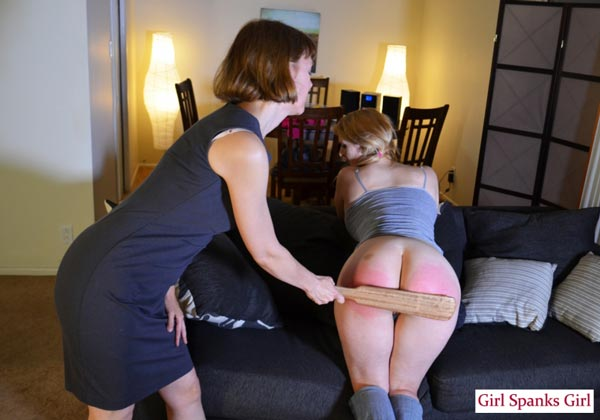 Clare paddles Ashley Rose's bare bottom with a thin wooden paddle