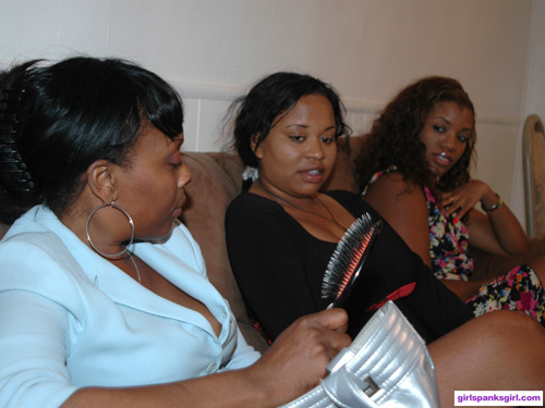 Lana shows her two ebony neices the hairbrush she uses for spankings