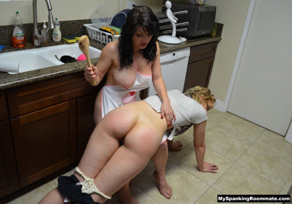 With one breast hanging out, Kay spanks Mia OTK with a wooden spoon