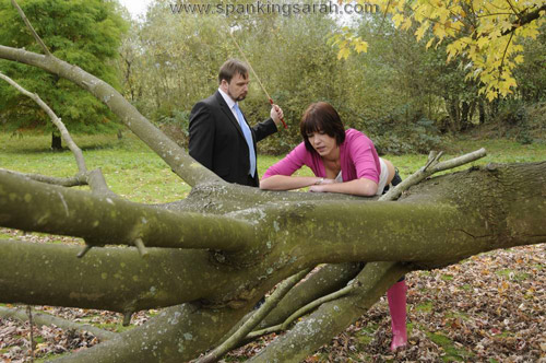 Sarah bends over a tree for the cane outdoors in the woods