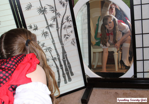 Christy Cutie watches herself in the mirror as Sarah spanks her bare bottom