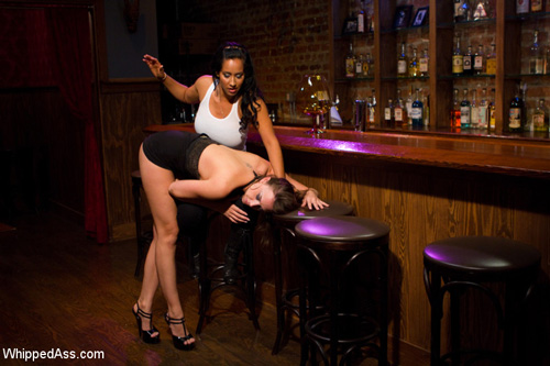 Hooker Chanel Preston bends over the barstool and gets spanked by Isis Love